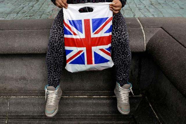 FILE PHOTO: A woman holds a Union Flag shopping bag in London, Britain April 23, 2016.  REUTERS/Kevin Coombs/File Photo