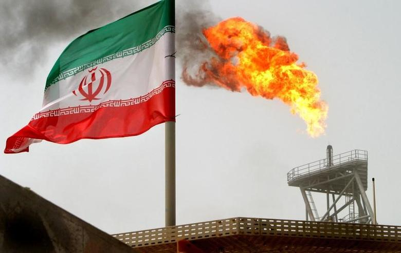 A gas flare on an oil production platform in the Soroush oil fields is seen alongside an Iranian flag in the Gulf July 25, 2005. REUTERS/Raheb Homavandi/Files