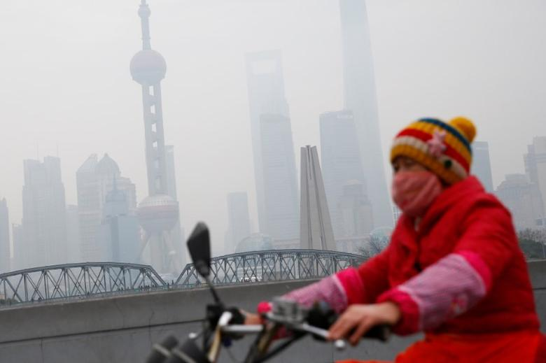 A woman wears a mask as she rides near the Bund during a polluted day in Shanghai, China, January 2, 2017.  REUTERS/Aly Song - RTX2X6WG