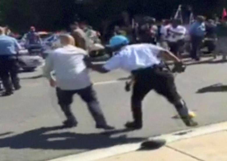 A Police officer push a man away from protesters, in this still image captured from a video footage, during a violent clash outside the Turkish ambassador's residence between protesters and Turkish security personnel during Turkish President Tayyip Erdogan's visit to Washington, DC, U.S. on May 16, 2017.   Courtesy Armenian National Committee of America/Handout via  REUTERS