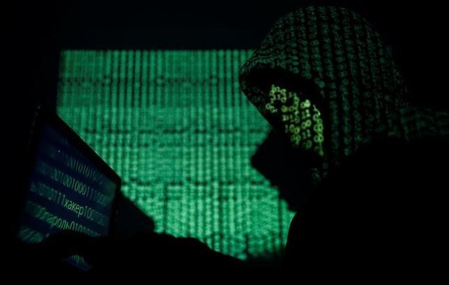 5月16日、わずか数時間で100カ国以上に拡散した身代金要求型ウイルス「WannaCry」はどのように始まり、これほど急速に拡散したのか。写真は、ノートパソコンを持つフードをかぶった人。ワルシャワで13日撮影(2017年 ロイター/Kacper Pempel)