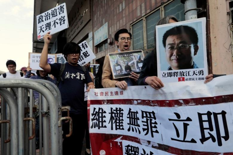 Pro-democracy demonstrators hold up portraits of Chinese disbarred lawyer Jiang Tianyong, demanding his release, during a demonstration outside the Chinese liaison office in Hong Kong, China December 23, 2016. REUTERS/Tyrone Siu/Files