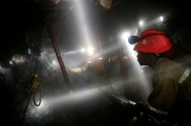 FILE PHOTO: Mine workers employed at Sibanye Gold's Masimthembe shaft operate a drill in Westonaria, South Africa, April 3, 2017.  REUTERS/Mike Hutchings/File Photo
