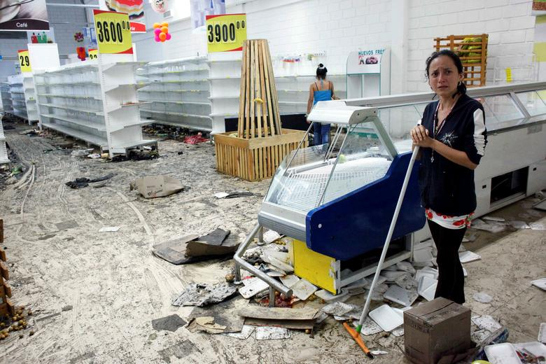 Workers clean the floor next to empty shelves and refrigerators in a supermarket after it was looted in San Cristobal, Venezuela May 17, 2017. REUTERS/Carlos Eduardo Ramirez