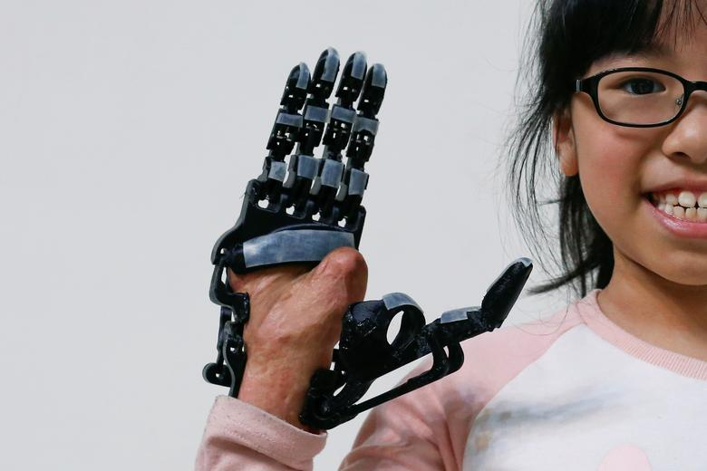 Angel Peng, 8, who injured her hand in a scalding accident when she was nine months old, poses for a photograph wearing a 3D-printed prosthetic hand designed and built by engineer Chang Hsien-Liang, in Taoyuan, Taiwan, April 6, 2017. REUTERS/Tyrone Siu