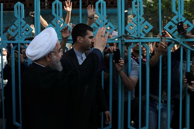 Iran's President Hassan Rouhani waves to supporters at a polling station during the presidential election in Tehran, Iran, May 19, 2017. President.ir/Handout via REUTERS