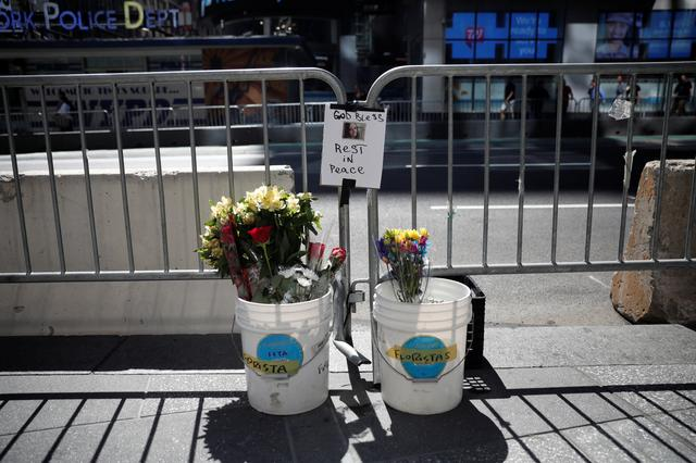 Flowers and a photograph of Alyssa Elsman, the 18-year-old woman who was killed when a speeding vehicle struck pedestrians on the sidewalk Thursday is seen at a makeshift memorial at the scene of the incident outside the 3 Times Square building in Times Square in New York City, U.S., May 19, 2017. REUTERS/Mike Segar