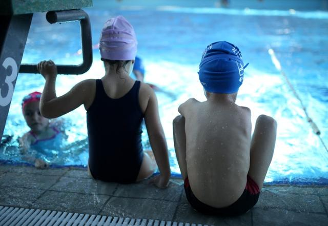 Ismail Zulfic (R), 6-year old armless swimmer sits by the pool in Olympic Pool Otoka in Sarajevo, May 18, 2017. Picture taken May 18, 2017. REUTERS/Dado Ruvic