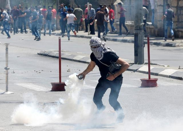 A Palestinian protester returns a gas canister fired by Israeli troops during clashes following a protest in support of Palestinian prisoners on hunger strike in Israeli jails, in the West Bank town of Bethlehem May 19, 2017. REUTERS/Ammar Awad