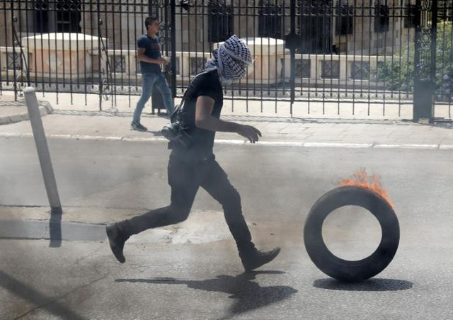 A Palestinian protester runs during clashes with Israeli troops following a protest in support of Palestinian prisoners on hunger strike in Israeli jails, in the West Bank town of Bethlehem May 19, 2017. REUTERS/Ammar Awad