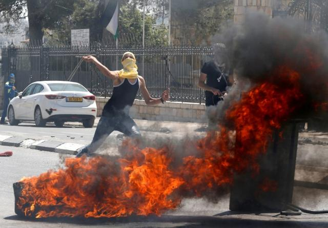 A Palestinian protester hurls stones at Israeli troops following a protest in support of Palestinian prisoners on hunger strike in Israeli jails, in the West Bank town of Bethlehem May 19, 2017. REUTERS/Ammar Awad