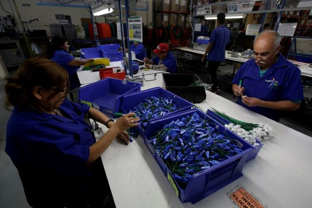 FILE PHOTO: Employees work at a wire harness and cable assembly manufacturing company that exports to the U.S. in Ciudad Juarez, Mexico, April 27, 2017. Picture taken April 27, 2017. REUTERS/Jose Luis Gonzalez/File photo