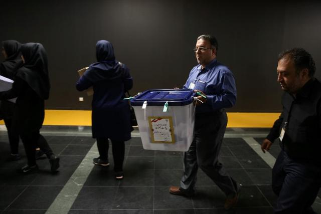 An electoral worker carries a ballot box after closing vote in a polling station in Tehran, Iran, May 19, 2017. TIMA via REUTERS