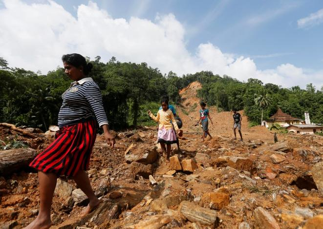 People walk through a landslide site during a rescue mission in Athwelthota village, in Kalutara, Sri Lanka May 28, 2017. REUTERS/Dinuka Li