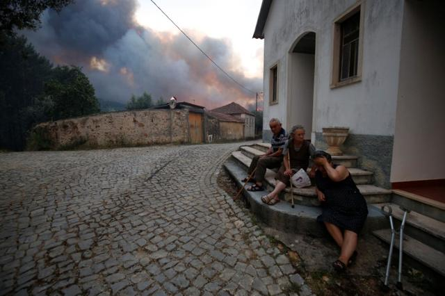 Villagers sit outdoors as a forest fire burns near the village of Fato, central Portugal, June 18, 2017. REUTERS/Rafael Marchante
