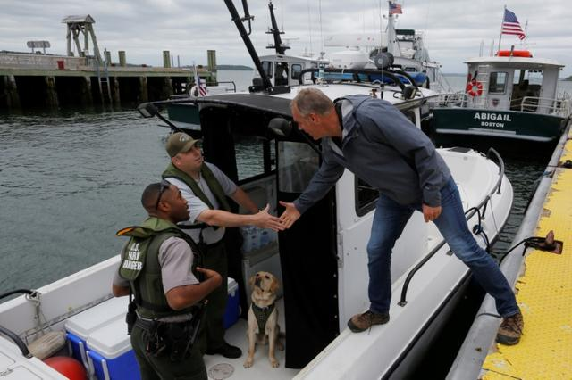 U.S. Interior Secretary Ryan Zinke (R) greets National Park Service Rangers in a patrol boat during a visit to Georges Island, part of his National Monuments review process, in Boston Harbor, Massachusetts, U.S., June 16, 2017.     REUTERS/Brian Snyder
