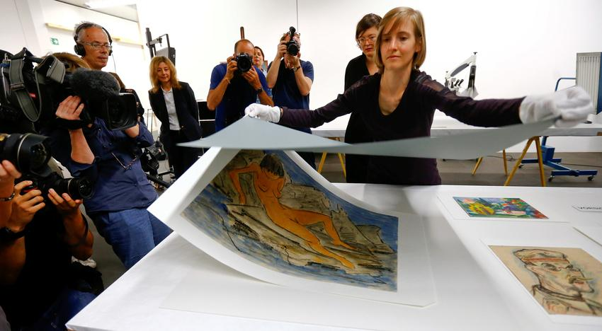 An employee removes a cover from the water colour painting 'Liegender weiblicher Akt am Wasser' by late German artist Otto Mueller during a news conference, after the arrival of the first artworks from the Dossier Gurlitt, at the Kunstmuseum Bern art museum in Bern, Switzerland July 7, 2017. Arnd Wiegmann
