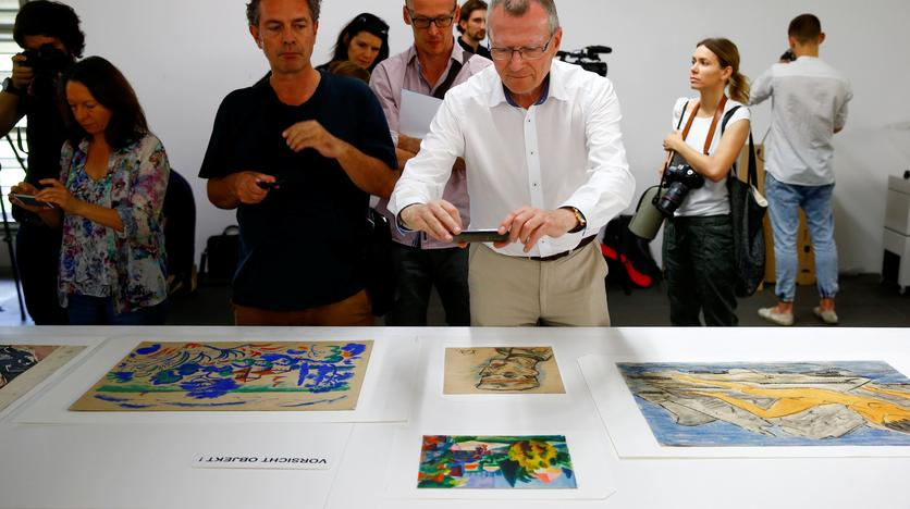 A journalist uses his mobile phone to takes a picture of a painting during a news conference, after the arrival of the first artworks from the Dossier Gurlitt, in Bern, Switzerland July 7, 2017. Arnd Wiegmann