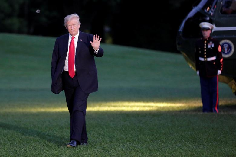 U.S. President Donald Trump waves as walks on the South Lawn of the White House upon his return to Washington, U.S., from the G20 Summit in Hamburg, July 8, 2017. REUTERS/Yuri Gripas
