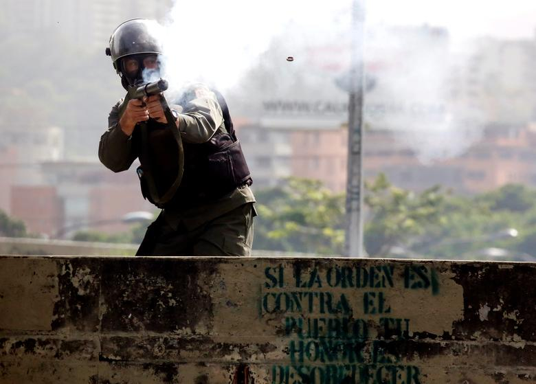 """A member of the security forces fires his gun during clashes at a protest against Venezuelan President Nicolas Maduro's government in Caracas, Venezuela. The graffiti below reads """"If the order is against the people your honour is to disobey"""". REUTERS/Carlos Garcia Rawlins"""