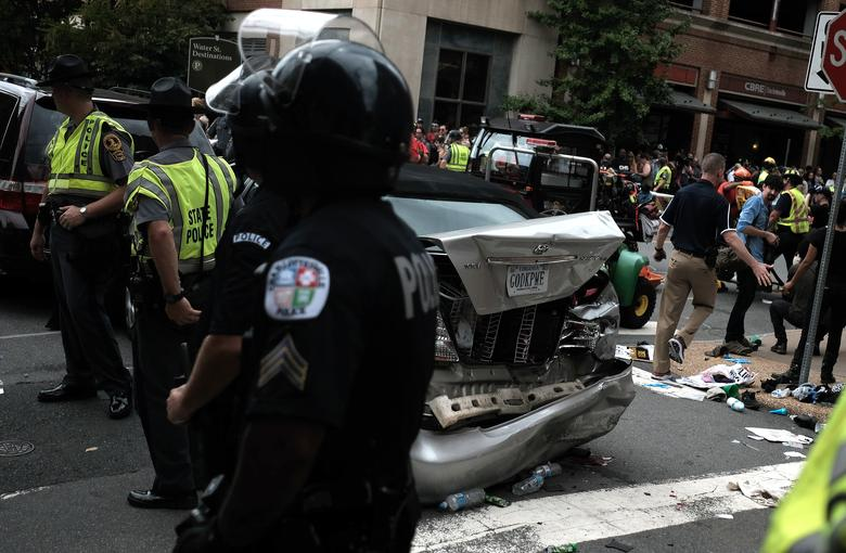 "First responders stand by a car that was struck when a car drove through a group of counter protesters at the ""Unite the Right"" rally. REUTERS/Justin Ide"