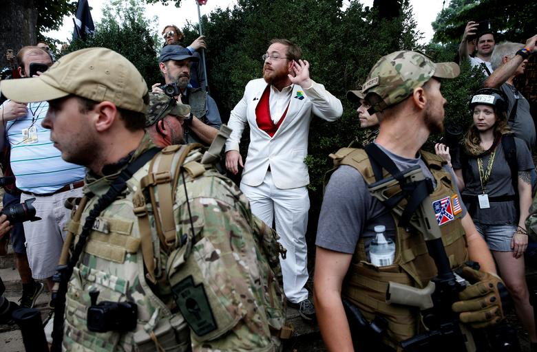 A white nationalist stands behind militia members after he scuffled with a counter demonstrator. REUTERS/Joshua Roberts