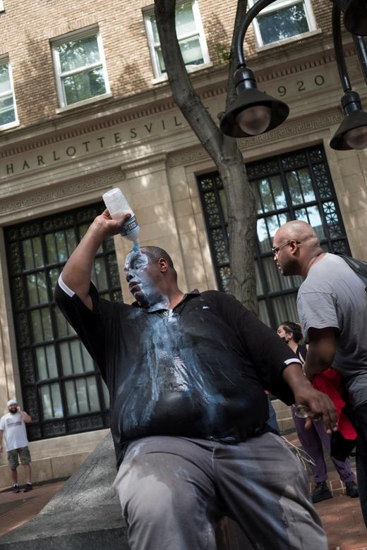 "A man applies liquid believed to be ""Milk of magnesia"" to treat pepper spray effects during a clash of a crowd of white nationalists against a group of counter-protesters. REUTERS/Justin Ide"