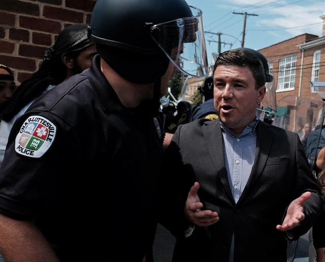 Unite The Right rally organizer Jason Kessler is escorted by police after he attempted to speak at a press conference in front of Charlottesville City Hall in Charlottesville, Virginia,  August 13, 2017. REUTERS/Justin Ide