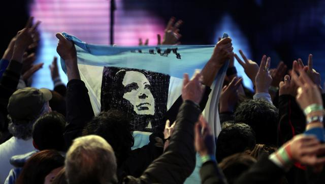 Supporters of Cristina Fernandez de Kirchner, former Argentine President and candidate for the Senate in the mid-term primary elections, display a flag with an image of her as they wait for her to appear at her campaign headquarters in Buenos Aires, Argentina August 14, 2017.  REUTERS/Marcos Brindicci