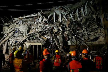 Rescuers work at the site of a collapsed building after an earthquake in...