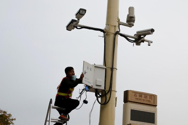 A man works on electrical wires in a box underneath surveillance cameras at Tiananmen Square in Beijing, China, October 12, 2017.  Thomas Peter -
