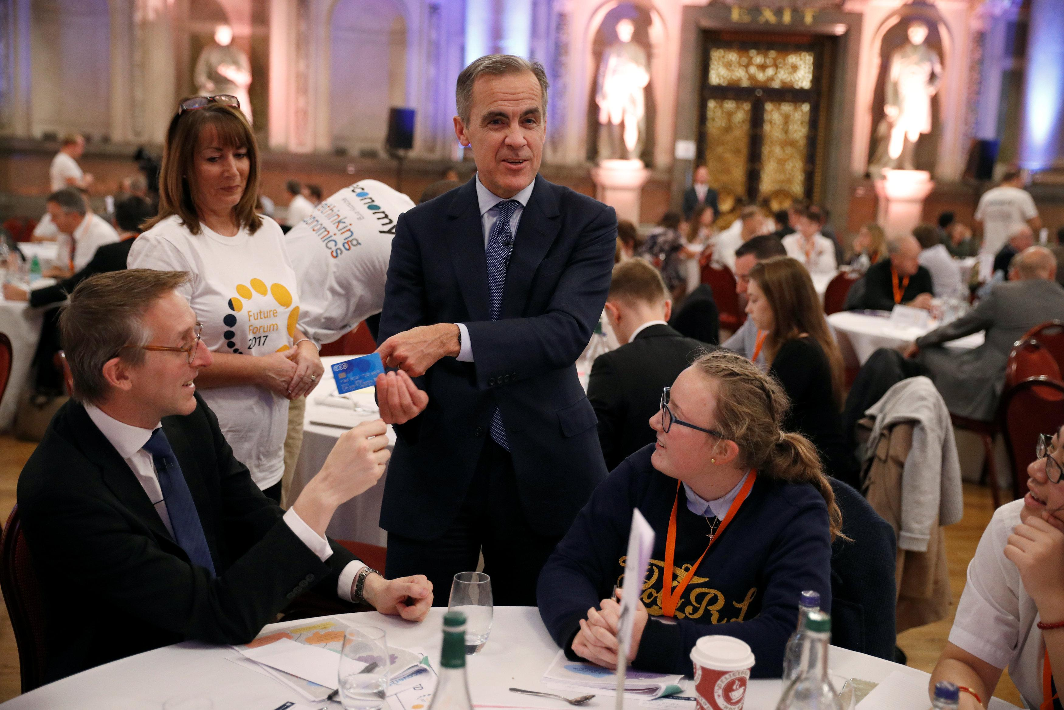 The Governor of the Bank of England, Mark Carney, holds a credit card as he speaks to guests during a meal at the