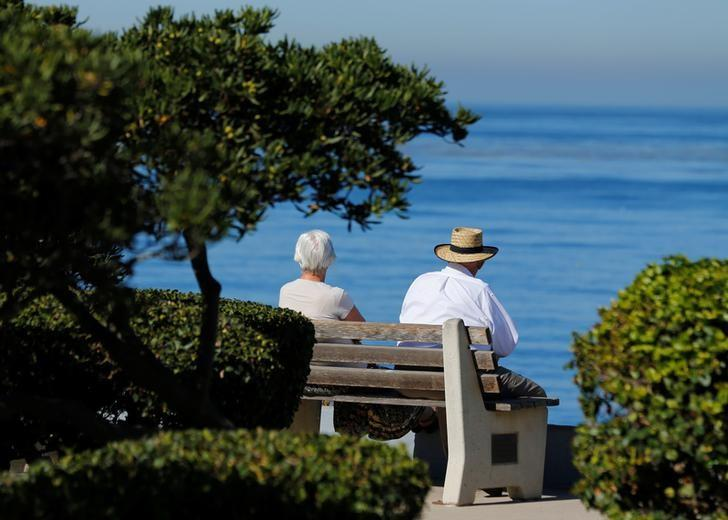 An elderly couple looks out at the ocean as they sit on a park bench in La Jolla, California November 13, 2013.   Mike Blake -