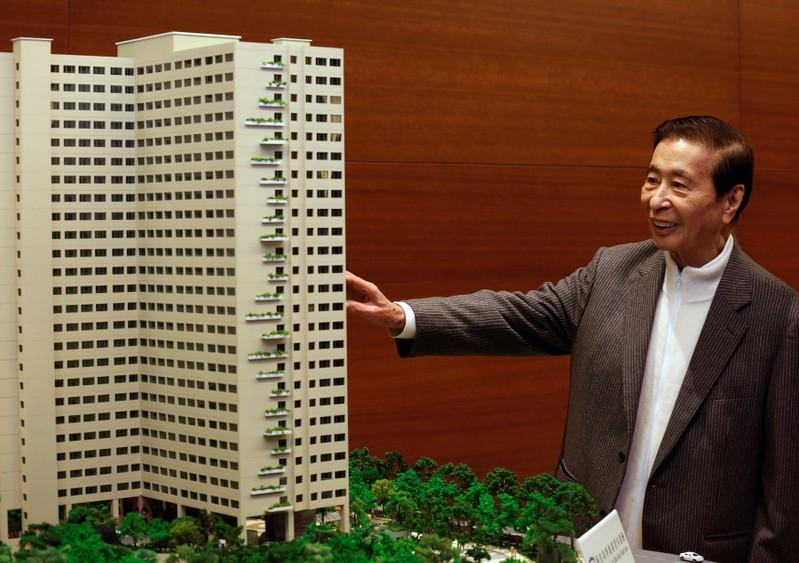 Tycoon Lee Shau-kee, founder, Chairman and Managing Director of property conglomerate Henderson Land Development Company Limited, poses in front of a building model during a news conference in Hong Kong January 15, 2015. Bobby Yip
