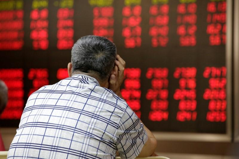 An investor looks at an electronic board showing stock information at a brokerage house in Beijing, China, June 24, 2016. Jason Lee