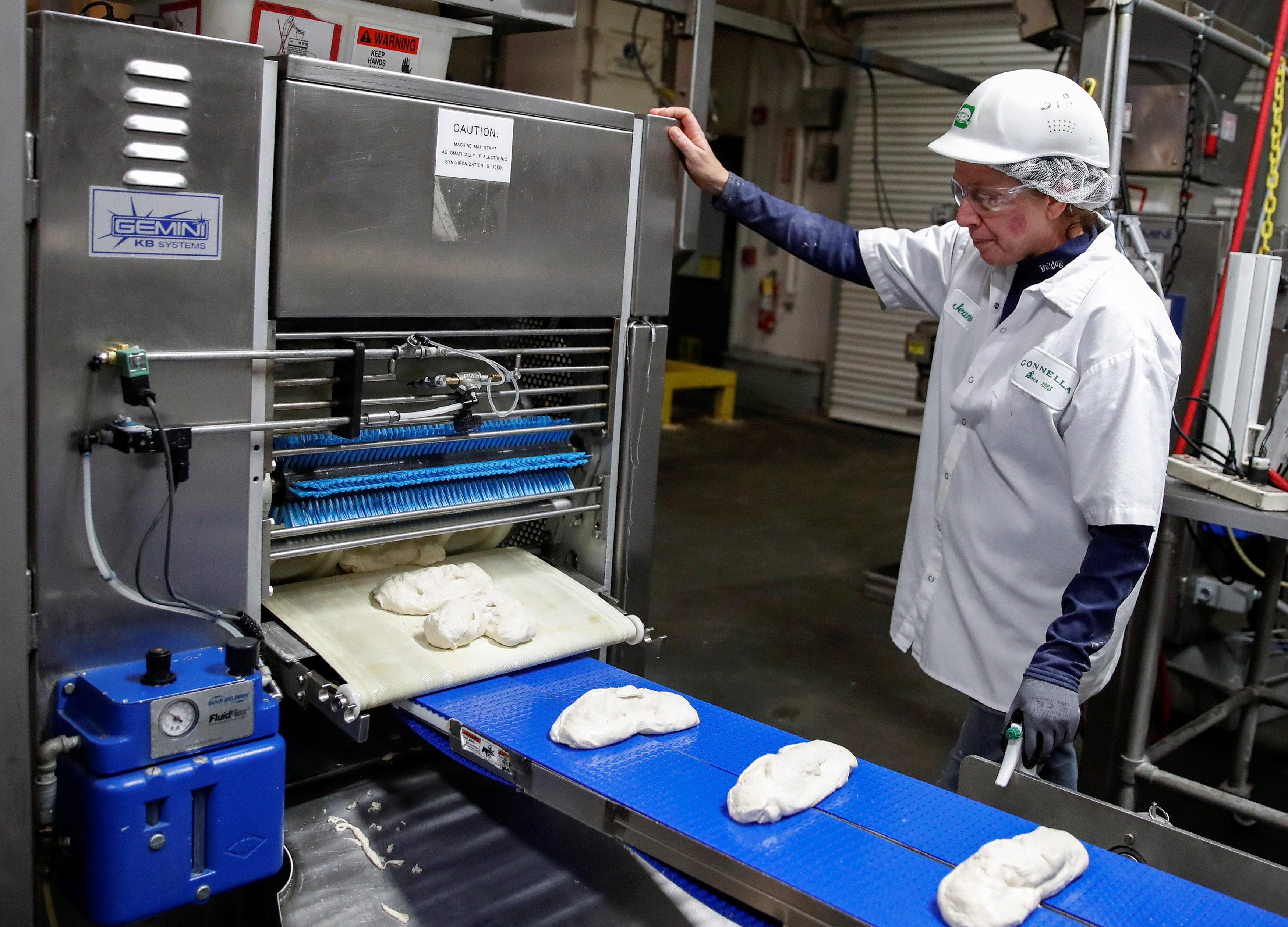 An employee checks on a dough during the production process at the Gonnella Baking Company in Aurora, Illinois, U.S., November 16, 2017. Picture taken November 16, 2017. Kamil Krzaczynski