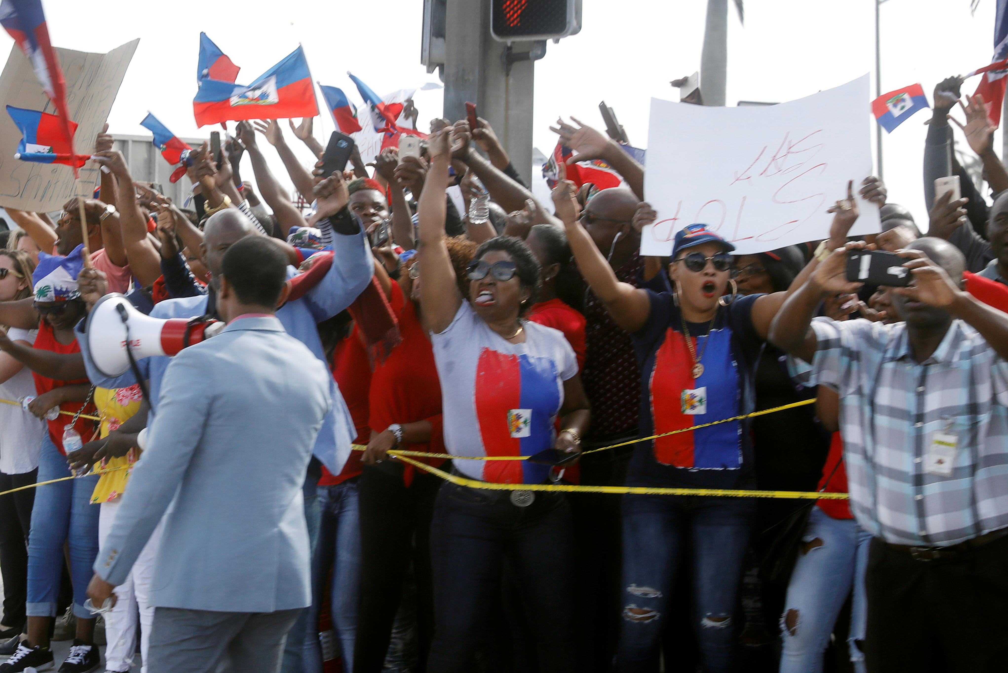 Demonstrators hold up Haitian flags and shout as the motorcade of U.S. President Donald Trump passes in West Palm Beach, Florida, U.S., January 15, 2018.  Kevin Lamarque