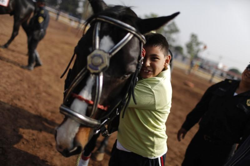A handicapped child embraces a horse after a session of equine-assisted therapy at the Mounted Police Unit in Mexico City May 15, 2013. Mexico City's Minister of Public Security (SSPDF) runs a free equine-assisted therapy program to help hundreds of children with autism, cerebral palsy, traumatic brain injury, stroke, emotional disturbances, eating disorders and substance abuse, according to local media. Picture taken May 15, 2013. Tomas Bravo