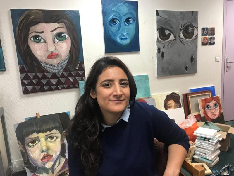Syrian artist Lina Aljijakli poses with her paintings in the Atelier for Artists in Exile in Paris, France, January 31, 2018. Aljijakli is one of around 150 artists from 20 countries supported by the atelier, an association in Paris that provides work space, supplies and exposure to artists seeking asylum in France.   Picture taken January 31, 2018.   Clotaire Achi