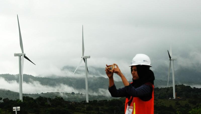 A woman takes pictures of wind power plant propeller blades in Sidenreng Rappang, Sulawesi Island of Indonesia, January 15, 2018. Antara Foto/Yusran Uccang via