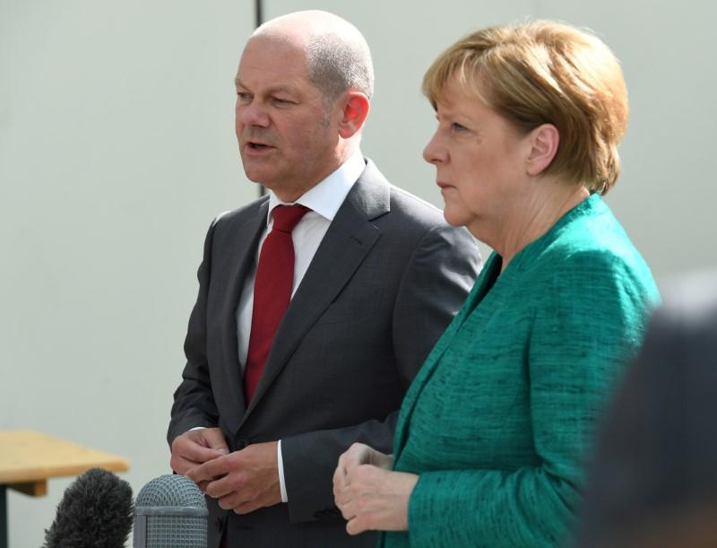 German Chancellor Angela Merkel and Mayor of Hamburg Olaf Scholz, who is slated to become finance minister in the new government coalition between Germany's Social Democrats and Merkel's conservative Christian Democrats. Patrik STOLLARZ