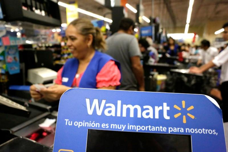 FILE PHOTO A cashier smiles beyond a Walmart logo during the kick-off of the 'El Buen Fin' (The Good Weekend) holiday shopping season, at a Walmart store in Monterrey, Mexico, November 17, 2017. Daniel Becerril