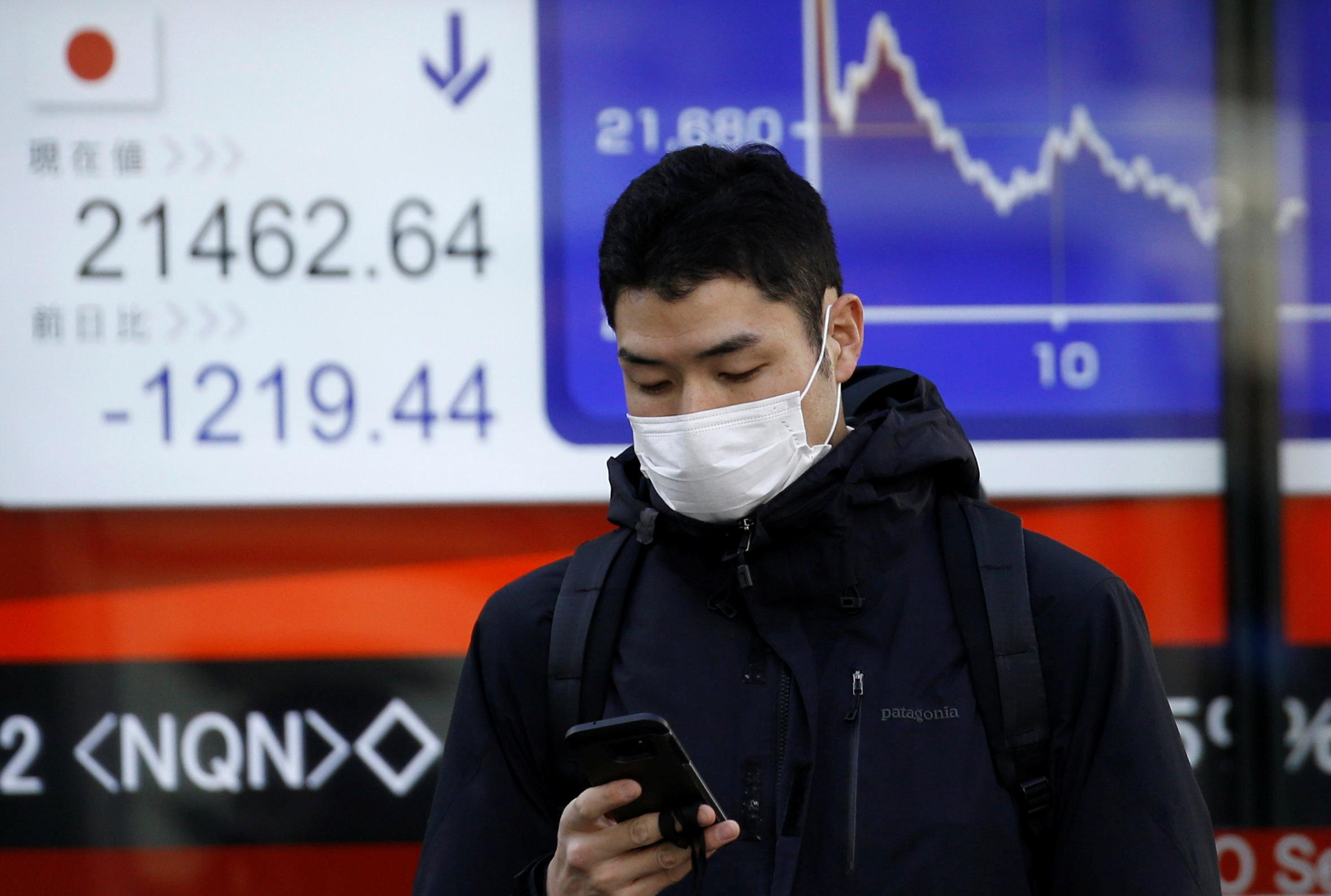 A man looks at a mobile phone in front of an electronic board showing Japan