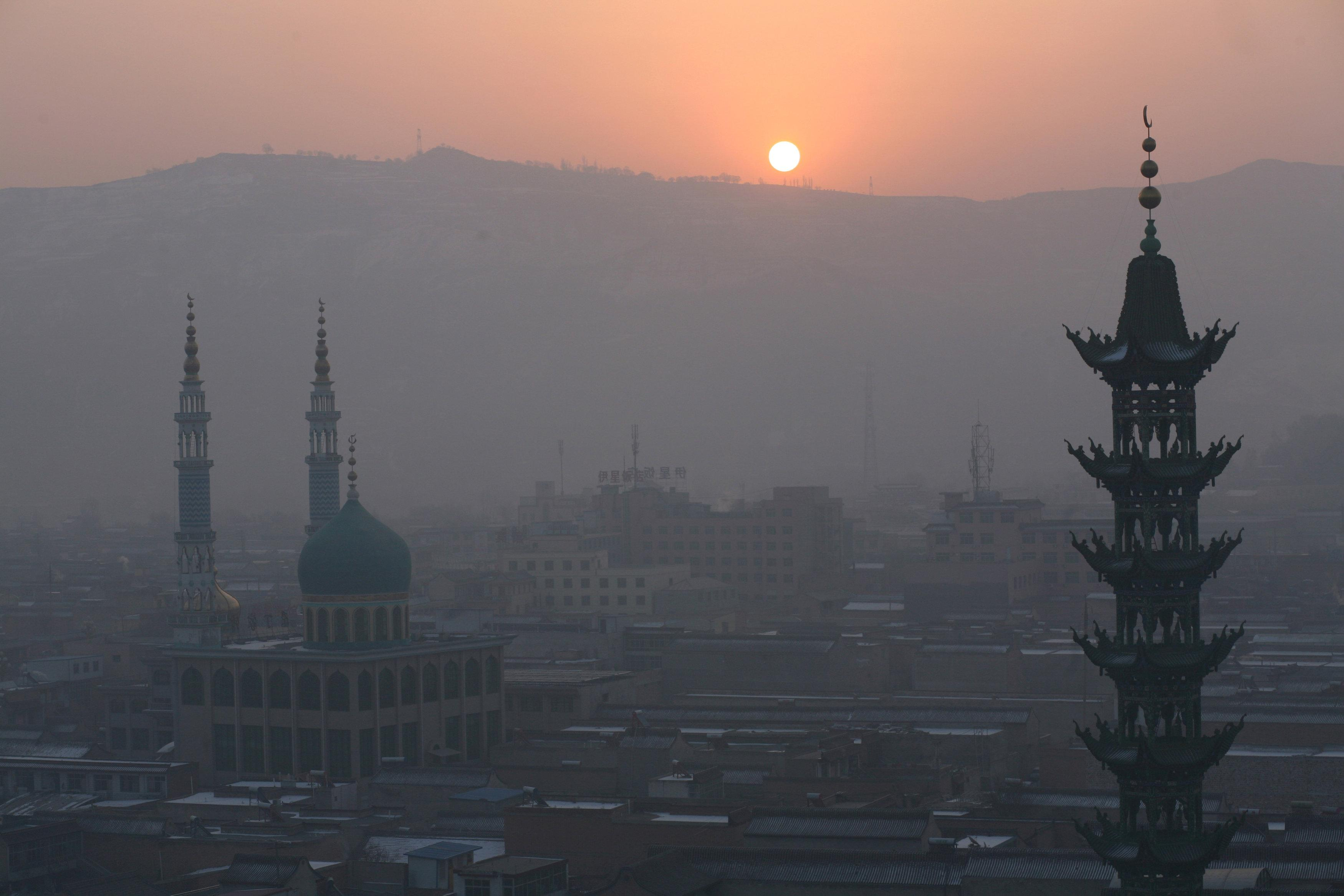 The sun rises over mountains and mosques in China's Linxia, Gansu province, home to a large population of ethnic minority Hui Muslims, February 3, 2018. Picture taken February 3, 2018. Michael Martina