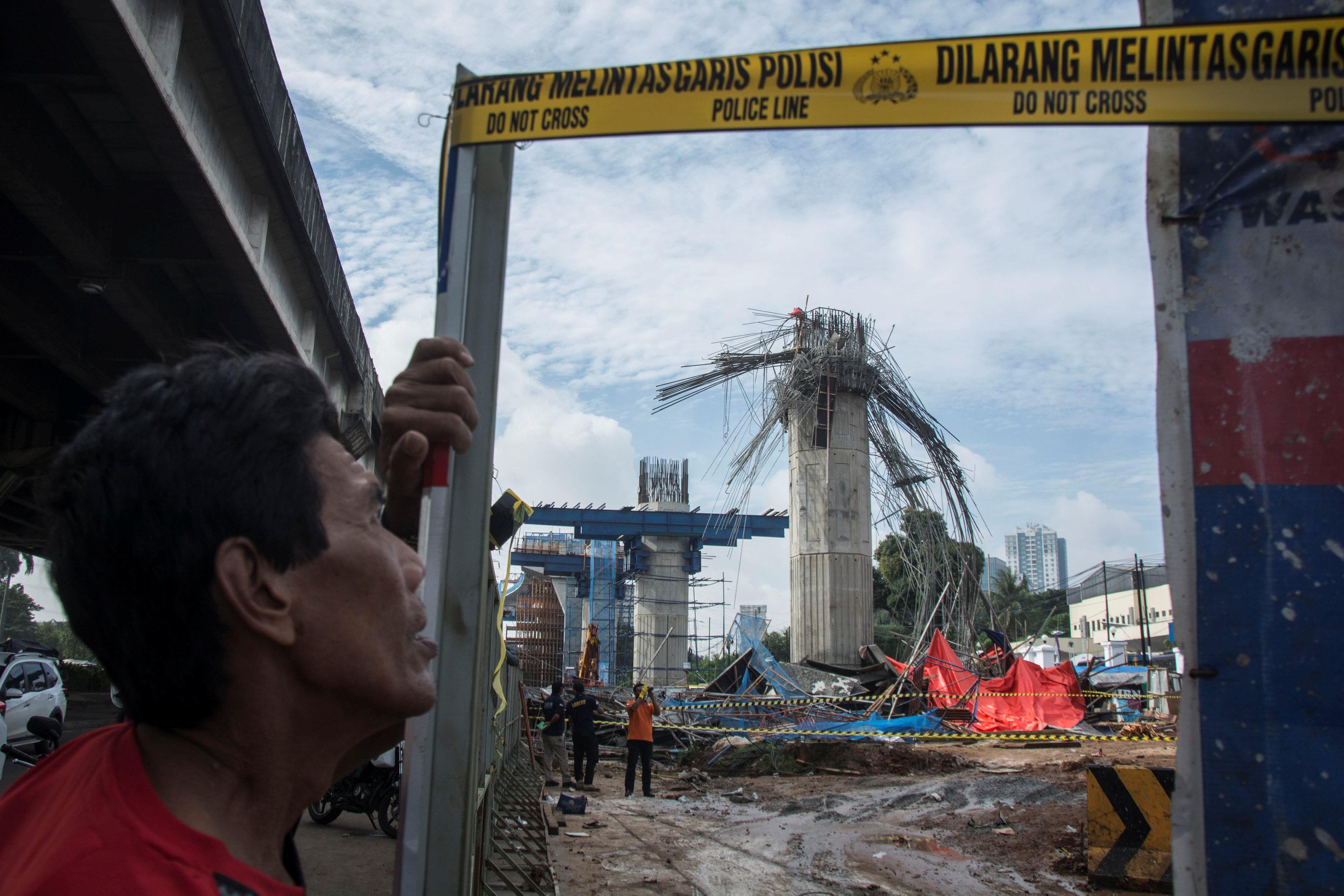 A man stands near a collapsed girder pole on the construction site of the Bekasi-Cawang toll overpass in Jakarta, Indonesia February 20, 2018 in this photo taken by Antara Foto.  Antara Foto/Aprillio Akbar/ via