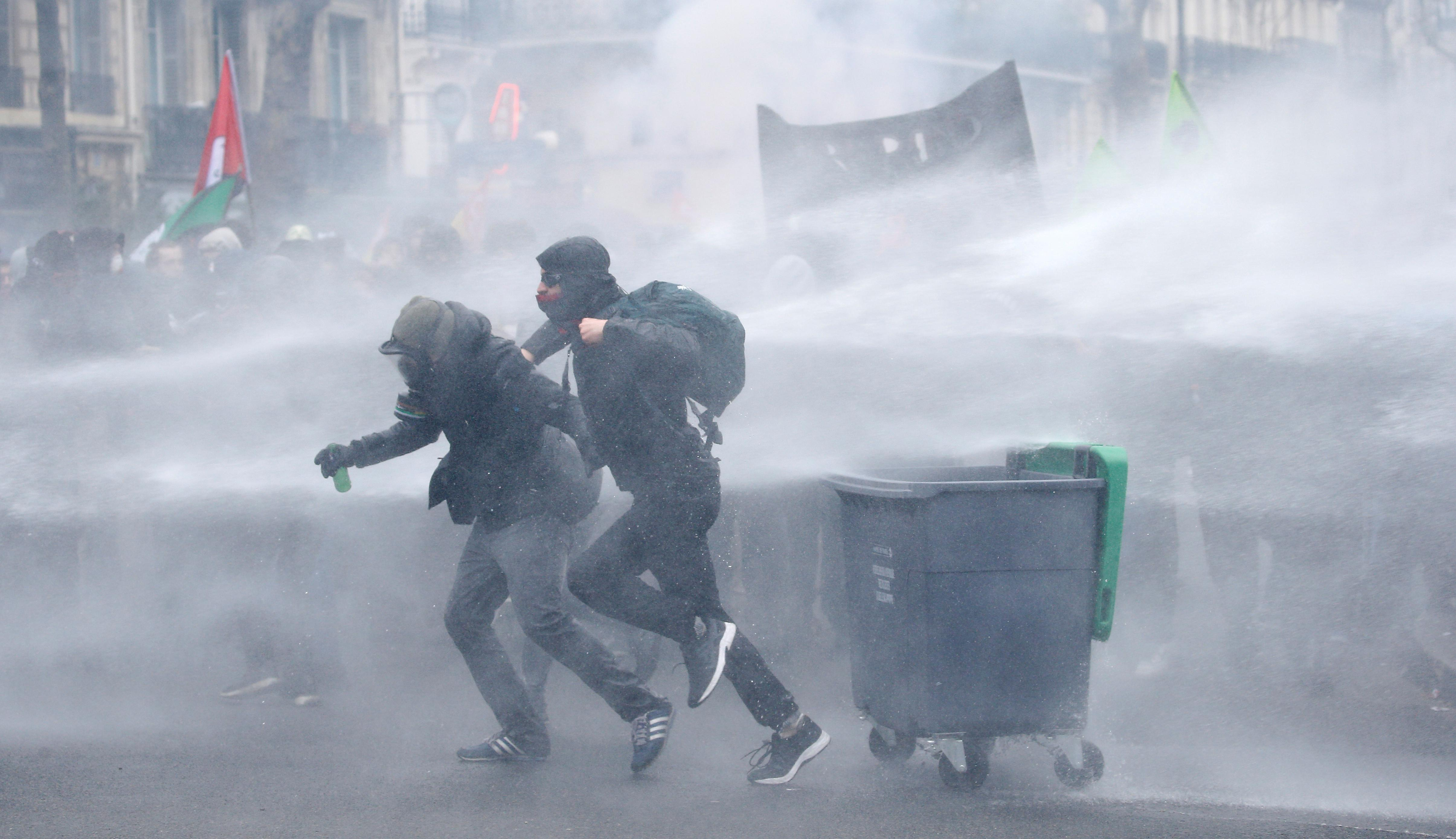 French riot police use water cannons during clashes with masked protesters attending a demonstration during a national day of strike against reforms in Paris, France, March 22, 2018.  Stephane Mahe