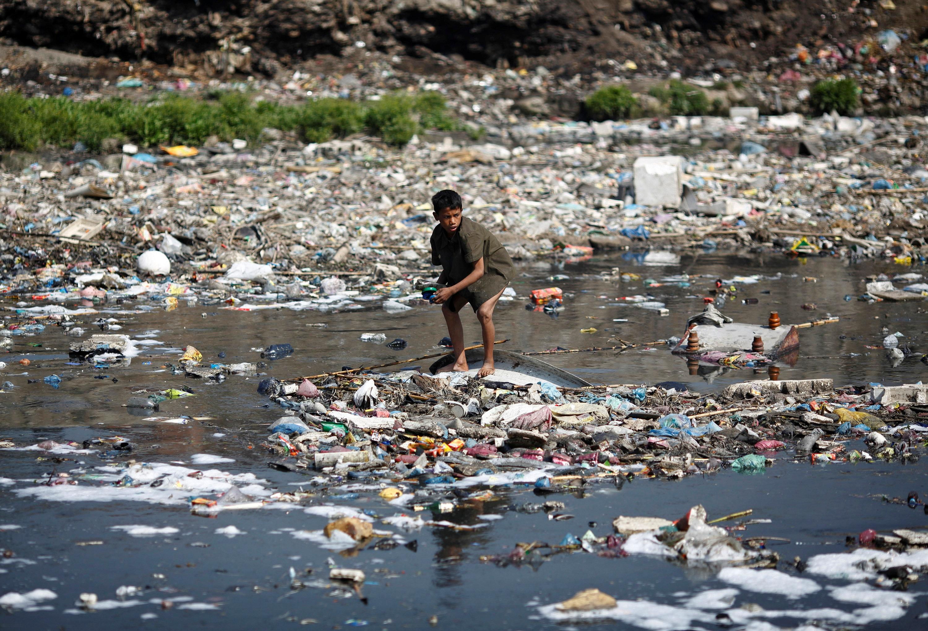 A boy looks for plastic bottles at the polluted Bagmati River in Kathmandu March 22, 2013. Navesh Chitrakar