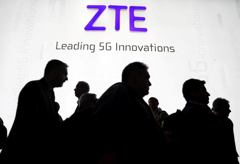 Visitors pass in front of the Chinese telecoms equipment group ZTE Corp booth at the Mobile World Congress in Barcelona, Spain, February 26, 2018. Sergio Perez