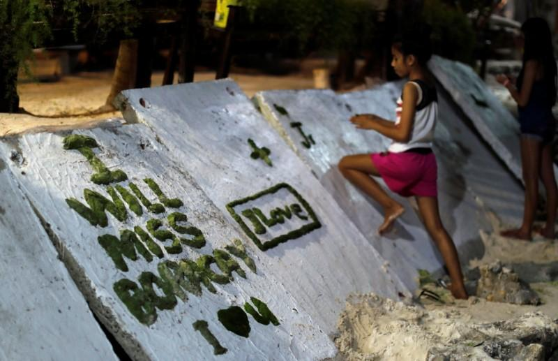 A girl scribbles on a wall two days before the temporary closure of the holiday island Boracay, in the Philippines April 24, 2018. Erik De Castro