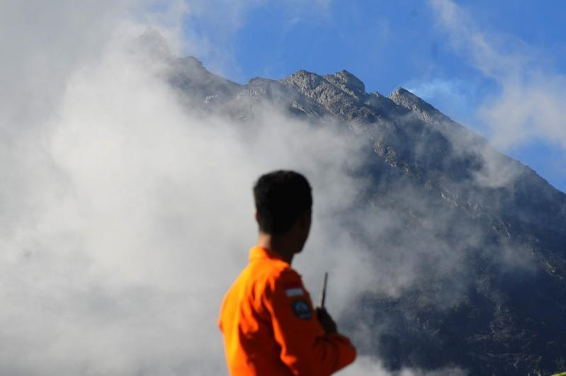 An officer from the National Search and Rescue Agency looks at Mount Merapi following a series of minor eruptions in Selo, Boyolali Regency, Central Java, Indonesia May 22, 2018 in this photo taken by Antara Foto.  Antara Foto/Aloysius Jarot Nugroho/via